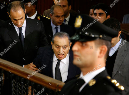 Hosni Mubarak, Alaa Mubarak, Gamal Mubarak. Former Egyptian President Hosni Mubarak, center, arrives with his sons Alaa, left, and Gamal, right, to testify, in a courtroom at the National Police Academy in Cairo, Egypt, . Two former Egyptian presidents appeared Wednesday in the same Cairo courtroom, with Mubarak testifying in a retrial of Mohammed Morsi on charges related to prison breaks at the height of the 2011 uprising that toppled Mubarak