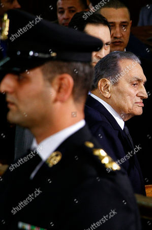 Stock Image of Former Egyptian President Hosni Mubarak, center, arrives with his sons Alaa, left, and Gamal, right, to testify, in a courtroom at the National Police Academy, in Cairo, Egypt, . Two former Egyptian presidents appeared Wednesday in the same Cairo courtroom, with Mubarak testifying in a retrial of Mohammed Morsi on charges related to prison breaks at the height of the 2011 uprising that toppled Mubarak