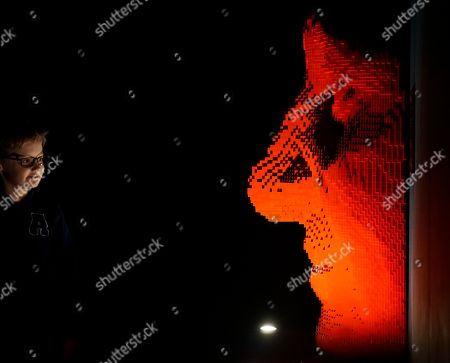 """A young visitor inspects a Lego sculpture entitled """"Red Facemask"""" by American artist Nathan Sawaya at the Palexpo convention center in Geneva on . The sculpture, one of several on display as part of a show called """"The Art of the Brick,"""" is made from more than 9,200 red Lego blocks"""