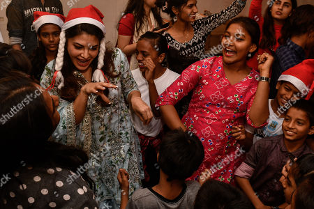 Stock Photo of Jacqueline Fernandez poses for a selfie with kids as she celebrates Christmas with children of St. Catherine Orphange, Mount Mary Road