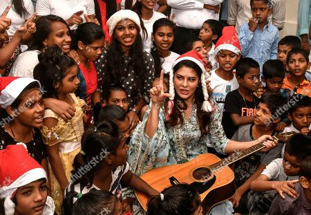 Jacqueline Fernandez poses for a selfie with kids as she celebrates Christmas with children of St. Catherine Orphange, Mount Mary Road