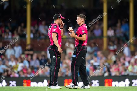 Sydney Sixers player Sean Abbott and Sydney Sixers player Moises Henriques discuss tactics