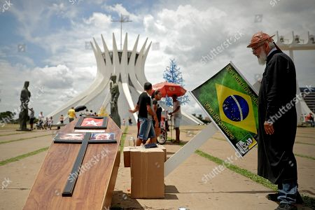 A supporter of Brazilian President-elect Jair Bolsonaro places a coffin with the photographs of the former Brazilian presidents Dilma Rousseff and Lula da Silva in the Esplanade of the Ministries, in Brasilia, Brazil, 27 December 2018. The far-right Bolsonaro, who will be inaugurated as president of Brazil on 01 January, won the presidential elections in Brazil on 28 October with 55.54% of the valid votes. Some half a million people are expected to watch Bolsonaro's investiture ceremony.