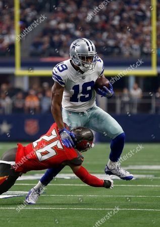 Amari Cooper, Andrew Adams. Dallas Cowboys wide receiver Amari Cooper (19) attempts to evade a tackle by Tampa Bay Buccaneers safety Andrew Adams (26) during the first half of an NFL football game in Arlington, Texas