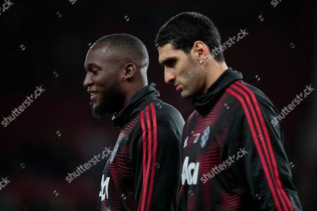 Manchester United forward Romelu Lukaku left smiles as he warms up with teammates including midfielder Marouane Fellaini