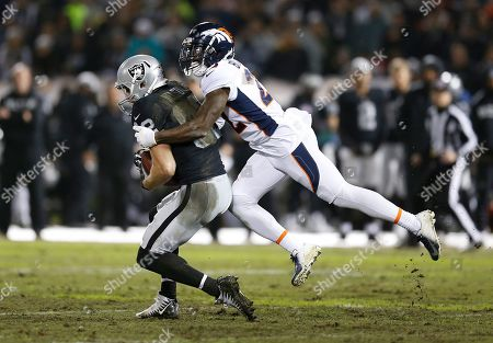 Oakland Raiders wide receiver Jordy Nelson, left, is tackled by Denver Broncos defensive back Tramaine Brock during the first half of an NFL football game in Oakland, Calif