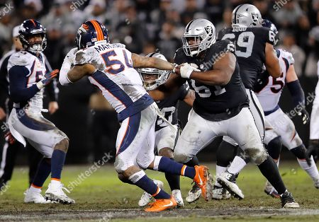 Oakland Raiders guard Rodney Hudson (61) tries to block Denver Broncos linebacker Brandon Marshall (54) during the second half of an NFL football game in Oakland, Calif