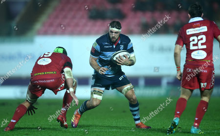Josh Turnbull of Cardiff Blues is tackled by Tom Price of Scarlets.