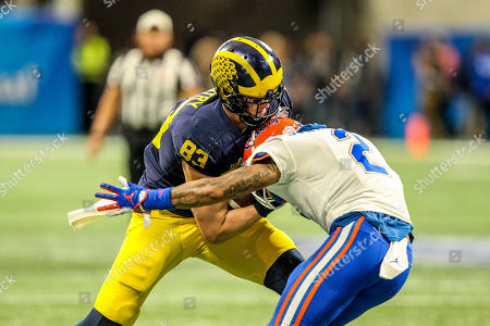 Michigan's Zach Gentry (83) is met by Florida's Brad Stewart, Jr (2) during the Chick-Fil-A Peach Bowl, featuring the Florida Gators and the Michigan Wolverines, played at Mercedes Benz Stadium in Atlanta, Georgia. Florida defeated Michigan, 41-15, to claim the Peach Bowl Championship