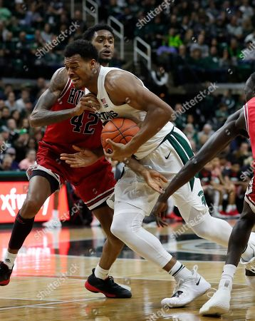 Michigan State forward Xavier Tillman drives on Northern Illinois forward Levi Bradley (42) during the second half of an NCAA college basketball game, in East Lansing, Mich