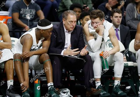 Michigan State head coach Tom Izzo talks with guards Cassius Winston, left, and Matt McQuaid during the second half of an NCAA college basketball game against Northern Illinois, in East Lansing, Mich