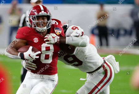 Josh Jacobs, Kenneth Murray. Alabama running back Josh Jacobs (8) is tackled by Oklahoma linebacker Kenneth Murray (9), during the first half of the Orange Bowl NCAA college football game, in Miami Gardens, Fla