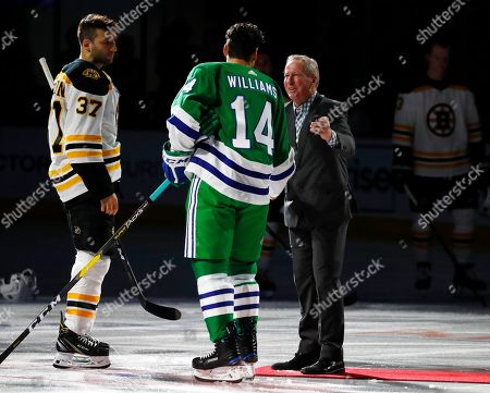 """Mike Rogers, Justin Williams, Patrice Bergeron. Mike Rogers, right, once the Hartford Whalers captain, speaks with Carolina Hurricanes' Justin Williams (14) and Boston Bruins' Patrice Bergeron (37) following a ceremonial puck drop prior to the start of """"Whalers night"""" at an NHL hockey game, in Raleigh, N.C"""