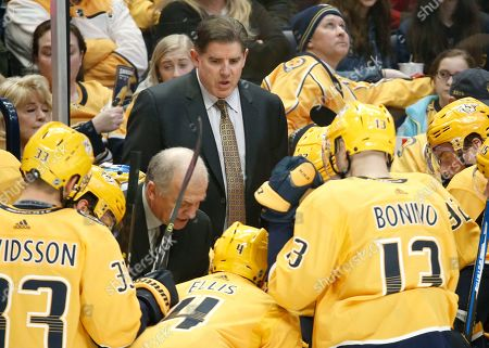 Nashville Predators coach Peter Laviolette, center, talks to players during a timeout in the third period of the team's NHL hockey game against the New York Rangers, in Nashville, Tenn. The Rangers won 4-3