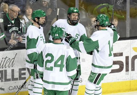 Stock Image of Teammates gather to congratulate North Dakota Fighting Hawks forward Casey Johnson (5) after he scored a goal during a exhibition men's college hockey game between the U.S. National Under-18 team and the University of North Dakota Fighting Hawks at Ralph Engelstad Arena in Grand Forks, ND. North Dakota was wearing replica 1959 team jerseys. UND won 6-2
