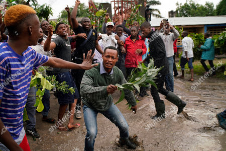 Congolese voters who have been waiting at the St. Raphael school in the Limete district of Kinshasa, heckle Corneille Nangaa, the president of the independent electoral commission (CENI) as he arrives to deliver the voters listings. People had started to gather at 6am to cast their votes, and four hours later, vote had not started as the lists were not available. Forty million voters are registered for a presidential race plagued by years of delay and persistent rumors of lack of preparation