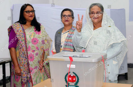 Stock Photo of Bangladeshi Prime Minister Sheikh Hasina (R) flashes the victory symbol after casting her vote, as her daughter Saima Wazed Hossain (L) and her sister Sheikh Rehana (C) look on at a polling station in Dhaka, Bangladesh, 30 December 2018. The last general election in Bangladesh was held in 2014. People are voting to select members of the national parliament, also known as Jatiya Sangsad.