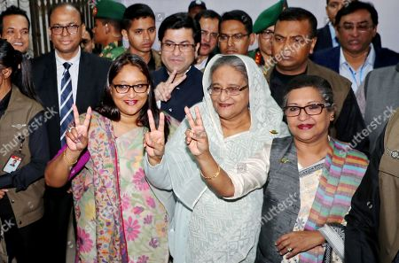 Bangladeshi Prime Minister Sheikh Hasina (C), her daughter Saima Wazed Hossain (L), and her sister Sheikh Rehana (R) flash the victory symbol after casting their vote at a polling station in Dhaka, Bangladesh, 30 December 2018. The last general election in Bangladesh was held in 2014. People are voting to select members of the national parliament, also known as Jatiya Sangsad.