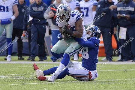 Dallas Cowboys' Rod Smith, top, is tackled by New York Giants' Tae Davis during the first half of an NFL football game Sunday, Dec., 30, 2018, in East Rutherford, N.J