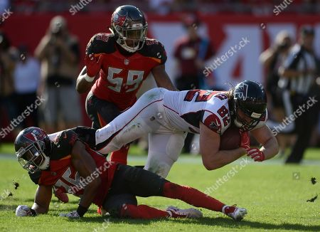 Atlanta Falcons tight end Logan Paulsen (82) gets hit by Tampa Bay Buccaneers defensive back Andrew Adams (26) and linebacker Devante Bond (59) during the second half of an NFL football game, in Tampa, Fla