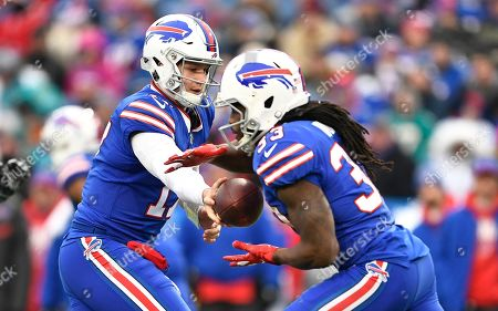 Stock Picture of Buffalo Bills quarterback Josh Allen, left, hands off the ball to running back Chris Ivory during the first half of an NFL football game against the Miami Dolphins, in Orchard Park, N.Y