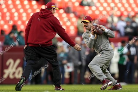 Washington Redskins passing game coordinator Kevin O'Connell, left, works with Washington Redskins quarterback Mark Sanchez during warmups before an NFL football game against the Philadelphia Eagles, in Landover, Md. The Eagles defeated the Redskins 24-0