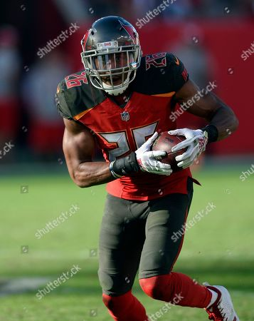 Tampa Bay Buccaneers defensive back Andrew Adams (26) runs with the football after intercepting a pass by Atlanta Falcons quarterback Matt Ryan during the second half of an NFL football game, in Tampa, Fla