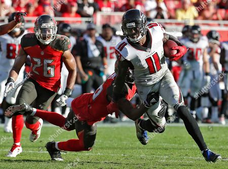 Atlanta Falcons wide receiver Julio Jones (11) is stopped by Tampa Bay Buccaneers cornerback M.J. Stewart (36) and defensive back Andrew Adams (26) after a reception during the second half of an NFL football game, in Tampa, Fla
