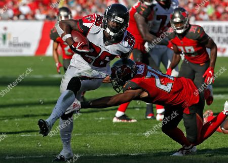 Atlanta Falcons running back Tevin Coleman (26) runs past Tampa Bay Buccaneers defensive back Andrew Adams for a score during the second half of an NFL football game, in Tampa, Fla