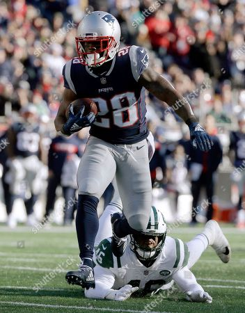 New England Patriots running back James White eludes New York Jets linebacker Neville Hewitt, right, on his way to a touchdown during the first half of an NFL football game, in Foxborough, Mass