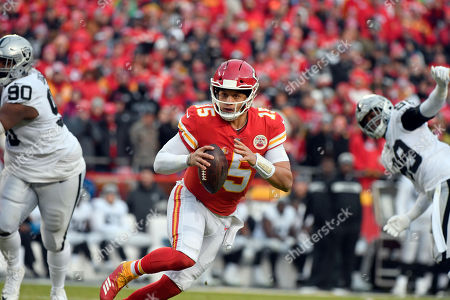 Kansas City Chiefs quarterback Patrick Mahomes (15) scrambles between Oakland Raiders defensive tackle Johnathan Hankins (90) and defensive end Arden Key (99) during the first half of an NFL football game in Kansas City, Mo