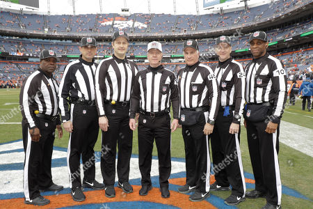 Officials pose before an NFL football game between the Los Angeles Chargers and the Denver Broncos, in Denver. They are, from right, line judge Julian Mapp (10), down judge David Olive, back judge Perry Paganelli (46), head linesman Patrick Turner (13), umpire Mark Pellis, field judge Matt Edwards, line judge Julien Mapp, and side judge Michael Banks
