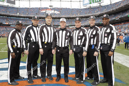 Officials pose before an NFL football game between the Los Angeles Chargers and the Denver Broncos, in Denver. They are, from right, line judge Julian Mapp (10), down judge David Olive, back judge Perry Paganelli (46), referee John Parry (132), umpire Mark Pellis, field judge Matt Edwards, line judge Julien Mapp, and side judge Michael Banks