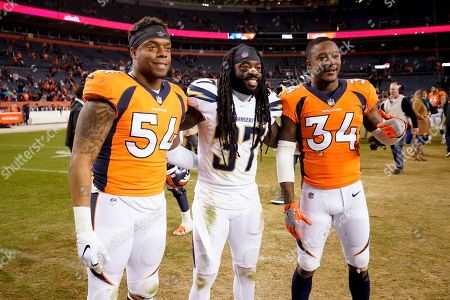 Los Angeles Chargers strong safety Jahleel Addae (37) poses with Denver Broncos strong safety Will Parks (34) and inside linebacker Brandon Marshall (54) after an NFL football game, in Denver