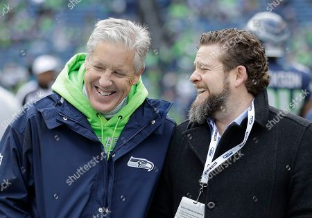Seattle Seahawks head coach Pete Carroll, left, talks with general manager John Schneider before the first half of an NFL football game against the Arizona Cardinals, in Seattle