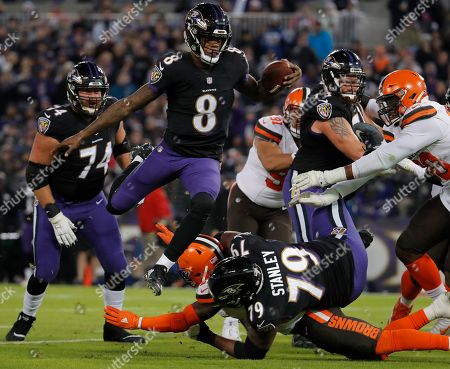 Baltimore Ravens quarterback Lamar Jackson (8) leaps over teammate Baltimore Ravens offensive tackle Ronnie Stanley (79) and a Cleveland Browns defender as he runs for a touchdown in the first half of an NFL football game against the Cleveland Browns, in Baltimore. Looking on is Baltimore Ravens offensive tackle James Hurst (74