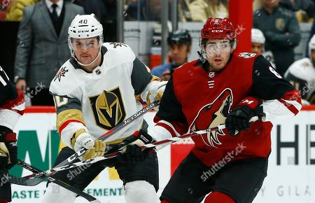Vegas Golden Knights center Ryan Carpenter (40) and Arizona Coyotes center Nick Schmaltz (8) battle for position during the first period of an NHL hockey game, in Glendale, Ariz