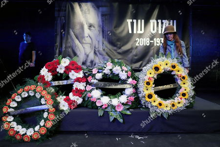 Stock Image of A woman lays flowers at the coffin of Israeli author Amos Oz during a memorial service at the Tzavta Theater in Tel Aviv, Israel, 31 December 2018. Amos Oz, an award-winning Israeli writer, published 40 books in his career and his works have been translated into 45 different languages. Oz died at the age of 79 after suffering from cancer on 28 December 2018.
