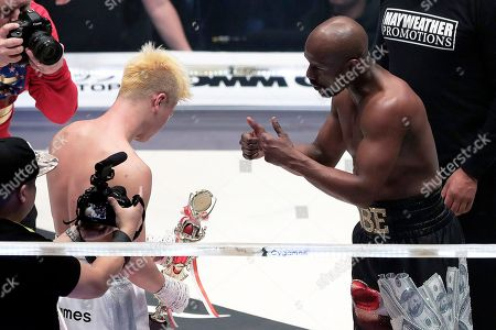 US former boxer Floyd Mayweather Jr. (R) gestures as he hands over a trophy he received to Japanese kickboxer Tenshin Nasukawa (L) after winning an exhibition boxing match during the RIZIN.14 mixed martial arts event at Saitama Super Arena in Saitama, north of Tokyo, Japan, 31 December 2018.