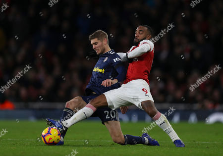 Stock Photo of Alexandre Lacazette of Arsenal reaches to get the ball ahead of Maxime Le Marchand of Fulham