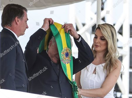 Brazilian President-elect Jair Bolsonaro (L) receives the presidential band from his predecessor, former Brazilian President Michel Temer (C), and former first lady Marcela Temer (R), during his inauguration ceremony at the Planalto Palace in Brasilia, Brazil, 01 January 2019. A far-right president leads the biggest Latin America democracy for first time since the end of military rule (1964-1985). Bolsonaro defeated candidate Fernando Haddad in the runoff, held last October, receiving 55 percent of the vote.