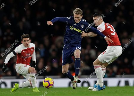 Arsenal's Granit Xhaka, right, challenges for the ball with Fulham's Andre Schuerrle during the English Premier League soccer match between Arsenal and Fulham at Emirates stadium in London
