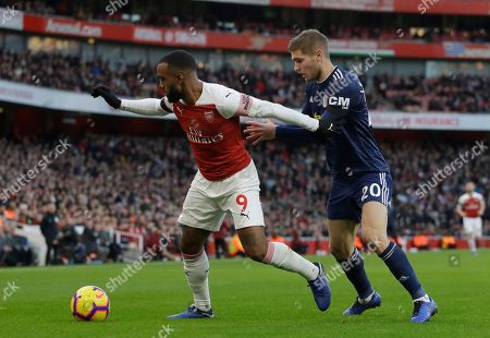 Arsenal's Alexandre Lacazette, left, challenges for the ball with Fulham's Maxime Le Marchand during the English Premier League soccer match between Arsenal and Fulham at Emirates stadium in London