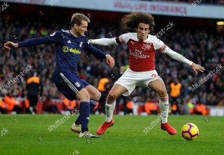 Fulham's Andre Schuerrle challenges for the ball with Arsenal's Matteo Guendouzi, right, during the English Premier League soccer match between Arsenal and Fulham at Emirates stadium in London
