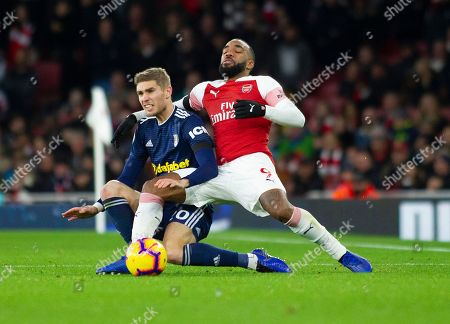 Maxime Le Marchand of Fulham and Alexandre Lacazette of Arsenal battle for the ball