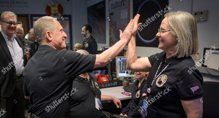 Stock Photo of New Horizons principal investigator Alan Stern, left, of the Southwest Research Institute in Boulder, Colo., left gives a high-five too New Horizons mission operations manager Alice Bowman, of the Johns Hopkins University Applied Physics Laboratory (APL), after the team received signals from the spacecraft that it is healthy and collected data, at the Mission Operations Center at the APL in Laurel, Md. The spacecraft survived a journey to near the tiny, icy object called Ultima Thule, about 4 billion miles from Earth