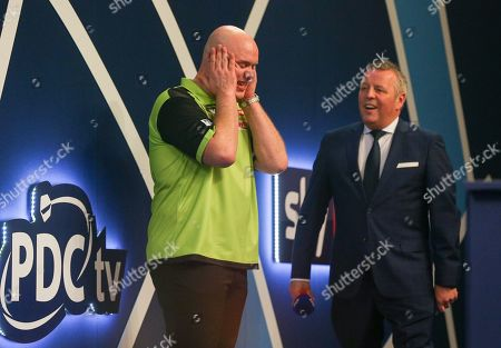 Michael van Gerwen celebrates and has his hands on his face after winning with John McDonald looking on during the 2019 William Hill World Darts Championship Final at Alexandra Palace, London