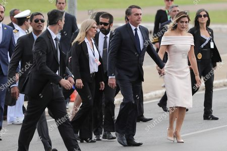 Brazilian President-elect Jair Bolsonaro (C) and wife Michele (C-R) head to a Rolls Royce that will take them to the Planalto Palace, where Bolsonaro will receive the presidential band from his predecessor, Michel Temer, in Brasilia, Brazil, 01 January 2019. A far-right president leads the biggest Latin America democracy for first time since the end of military rule (1964-1985). Bolsonaro defeated candidate Fernando Haddad in the runoff, held last October, receiving 55 percent of the vote.