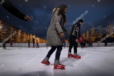 People enjoy ice skating on a rink during the first day of the year at the Stavros Niarchos Foundation Cultural Center in Athens, on