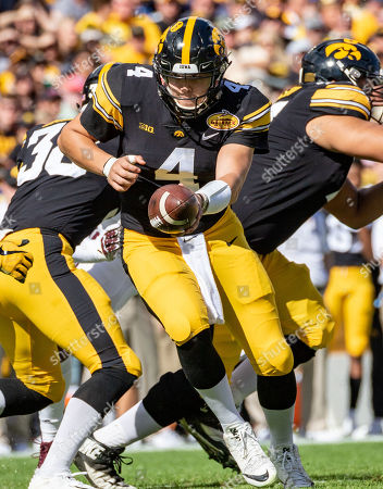 Stock Image of Iowa Hawkeyes quarterback Nate Stanley (4) hands the ball off in the 1st quarter during the game between the Mississippi State Bulldogs and the Iowa Hawkeyes in the Outback Bowl at Raymond James Stadium in Tampa, Florida